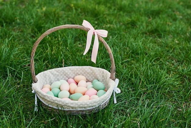 Wielkanocny kosz na wiosny zielonej trawie. słodkie jajko. polowanie na pisanki. szczęśliwy wielkanocny kartka z pozdrowieniami z copyspace. wielkanocny kartka z pozdrowieniami szablon jajka na trawie wiosny wakacyjny pojęcie z kopii przestrzenią