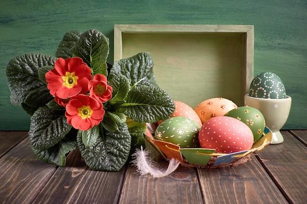 Wielkanocny kosz z malującymi wielkanocnymi jajkami i czerwonym pierwiosnkowym garnka kwiatem na nieociosanym drewnie