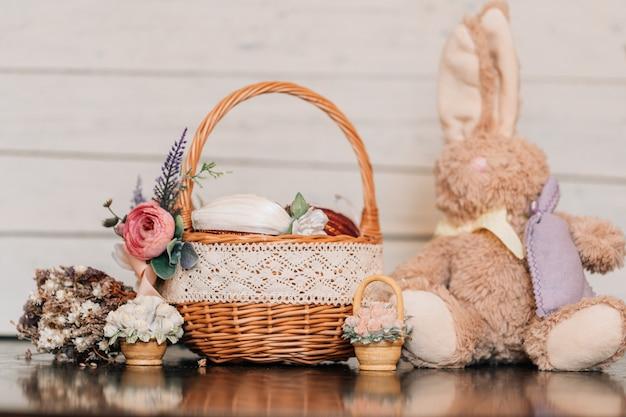 Wielkanocny kosz z zdobionymi jajkami i pluszowy królik na drewnianym stole.