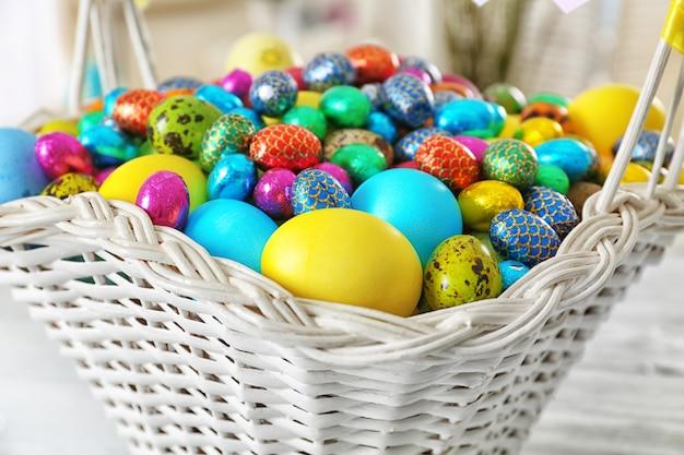 Wielkanocny koszyk z kolorowymi jajkami na stole, zbliżenie