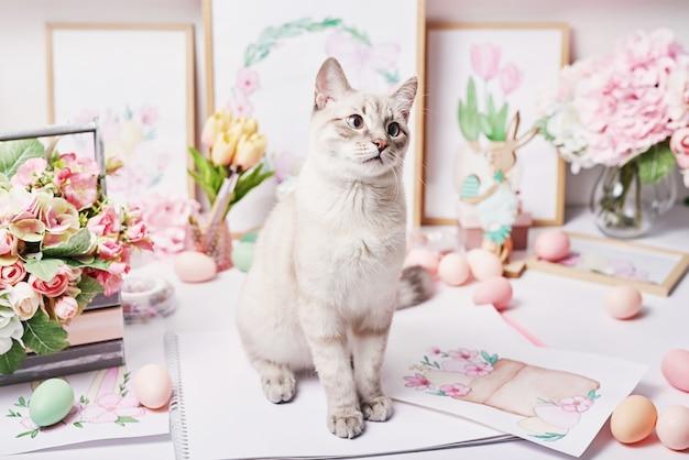Wielkanocny kot z jajkami i kwiatami. szary kotek siedzi na stole. wiosna z życzeniami wesołych świąt. wystrój wielkanocny. akwarele wiosenne. miejsce pracy projektanta i artysty. kreatywna przestrzeń.