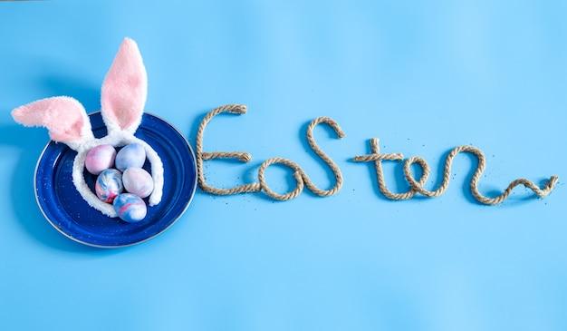 Wielkanocny kreatywny napis na niebieskim tle.
