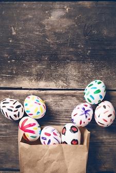 Wielkanocny królik w papierowej torbie na starych deskach