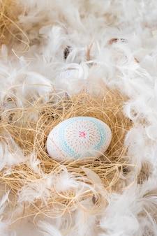 Wielkanocny kurczaka jajko na sianie między rozsypiskiem piórka