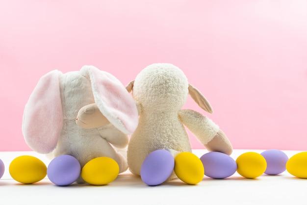 Wielkanocny mały królik królik przytulić przyjaciela królika z zdobionymi jajkami