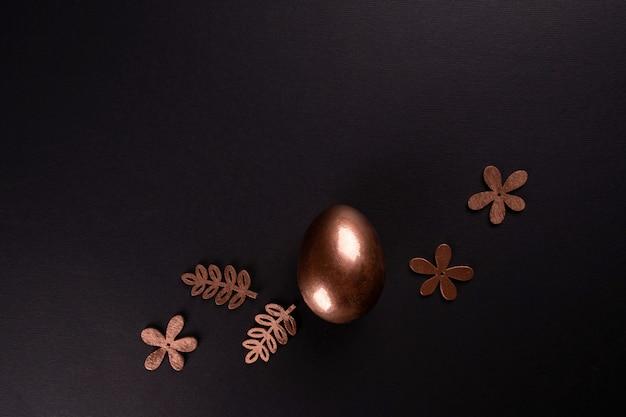 Wielkanocny minimalny tło z złocistymi wielkanocnymi jajkami na czarnym tle. leżał płasko, widok z góry, miejsce.