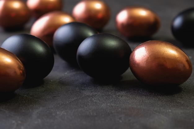 Wielkanocny minimalny tło z złotymi i czarnymi wielkanocnymi jajkami na czarnym tle. leżał płasko, widok z góry, miejsce.