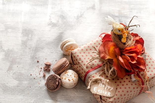 Wielkanocny prezent i słodycze na drewnianym tle.