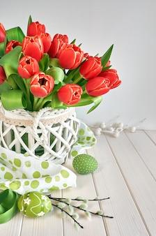 Wielkanocny projekt kartki z bukietem czerwonych tulipanów na jasnej wiośnie z jasnozielonymi dekoracjami wielkanocnymi,