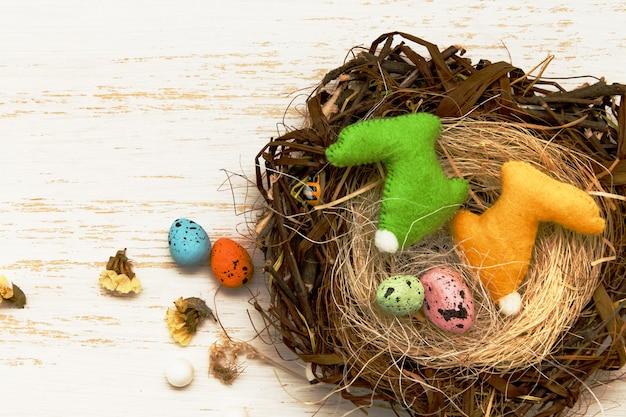 Wielkanocny skład gniazduje t króliki na drewnianym stole