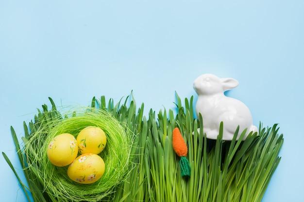 Wielkanocny skład kolorowi jajka w gniazdeczku i królik w trawie.