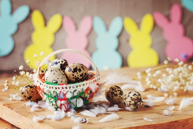 Wielkanocny skład wielkanocni jajka przepiórczy w koszu i z królik girlandą na drewnianym