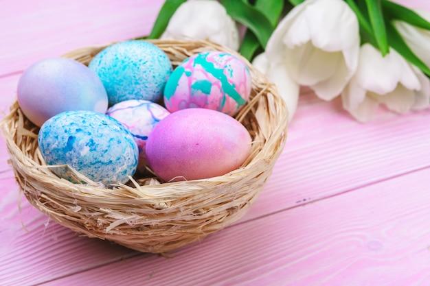 Wielkanocny stół z kolorowymi jajkami i tulipanami nad różowym drewnem. widok z góry z miejsca kopiowania