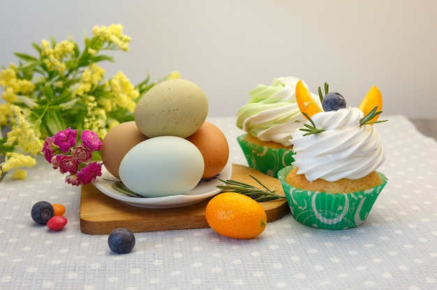 Wielkanocny świąteczny stół deserowy z babeczkami, jajkami i słodyczami.