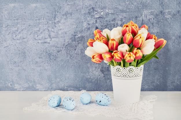 Wielkanocny tło. dekoracyjni wielkanocni jajka i czerwoni tulipany w wazie. skopiuj miejsce