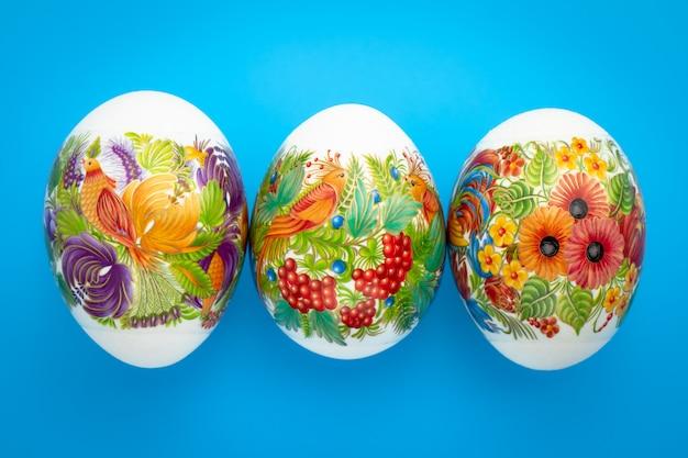 Wielkanocny tło kolorowe jaja paschalne z ornamentem na niebieskim tle. świąteczne wydarzenie. wiosna. karta podarunkowa, koncepcja tradycji chrześcijańskiej.