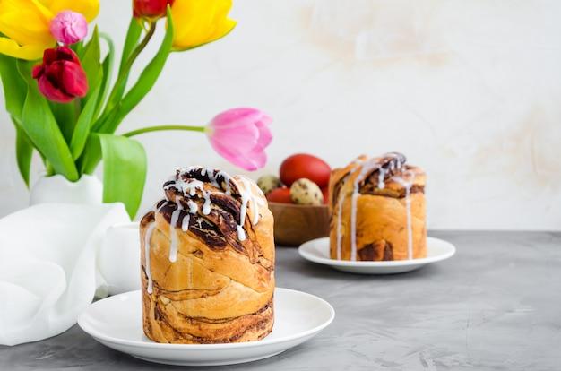 Wielkanocny tło wielkanocny tort z czekoladową dokrętką śmietanką i cukrowym glazerunkiem na górze na białym talerzu na betonowym tle. orientacja pozioma. skopiuj miejsce