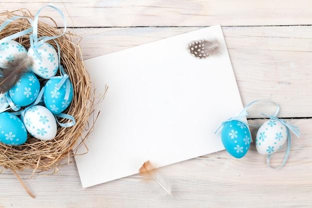 Wielkanocny tło z błękitnymi i białymi jajkami w gniazdeczku i kartka z pozdrowieniami