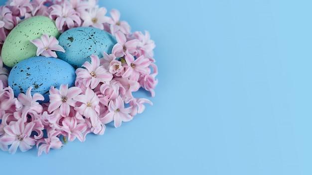 Wielkanocny tło z błękitnymi wielkanocnymi jajkami w gniazdeczku wiosna kwitnie.