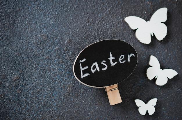 Wielkanocny tło z dekoracyjnymi drewnianymi motylami i wpisową wielkanocą.