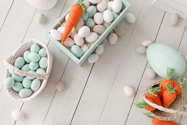 Wielkanocny tło z kolorowymi jajkami i żółtymi pomarańczowymi marchewkami nad białym drewnem.