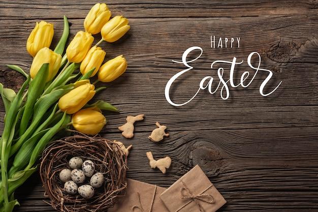 Wielkanocny tło z kolorowymi jajkami i żółtymi tulipanami na drewnianym stole, odgórny widok