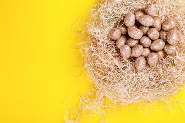 Wielkanocny tło z złotą farbą easter jajka w gniazdeczku