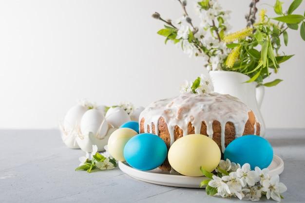 Wielkanocny tort, barwioni jajka na wydarzenie rodzinnym stole z czereśniowymi kwiatami kwitnie. miejsce na tekst.