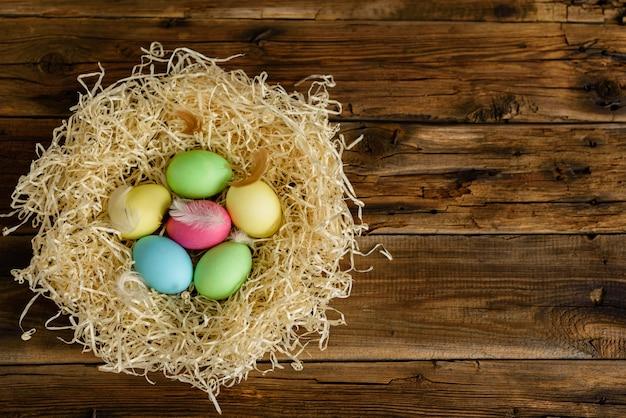 Wielkanocny tort i kolorowi jajka na drewnianym stole.