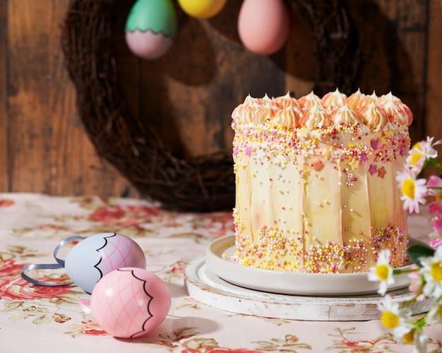 Wielkanocny tort ozdobiony posypką na drewnianym tle.