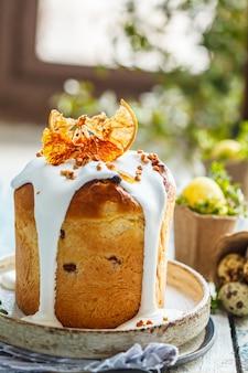 Wielkanocny tort z lodowaceniem i pomarańcze na błękitnym drewnianym stole.