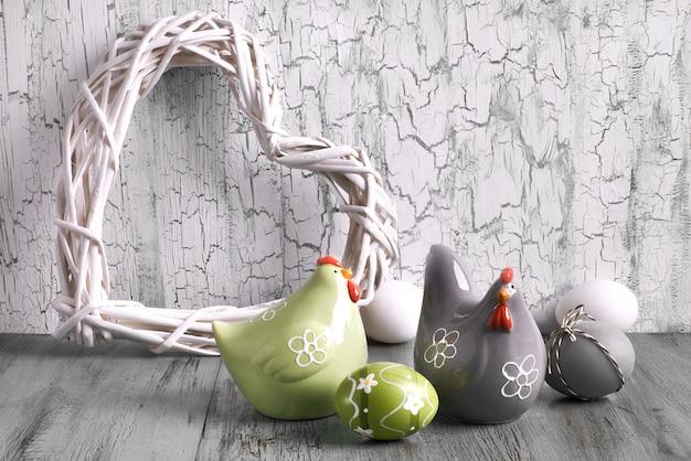 Wielkanocny układ z drewnianym sercem, ceramicznymi kurami i białymi jajkami na pękniętym chwastach