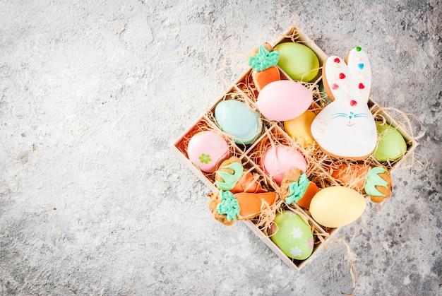 Wielkanocny wakacyjny pojęcie, słodcy ciastka w postaci marchewek, wielkanocny królik z kolorowymi jajkami, odgórny widok, szarości tła kopii kamienna przestrzeń