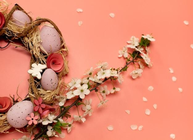 Wielkanocny wieniec z kolorowymi ozdobnymi jajkami i gałązką świeżych wiosennych kwiatów z płatkami na różowym tle