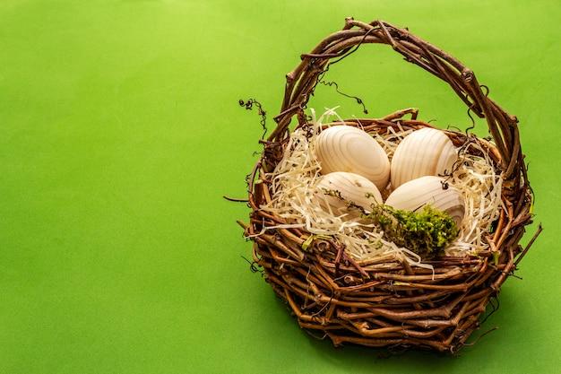 Wielkanocny wiklinowy kosz. zero odpadów, koncepcja diy. drewniane jajka, wióry, mech. jasne zielone tło