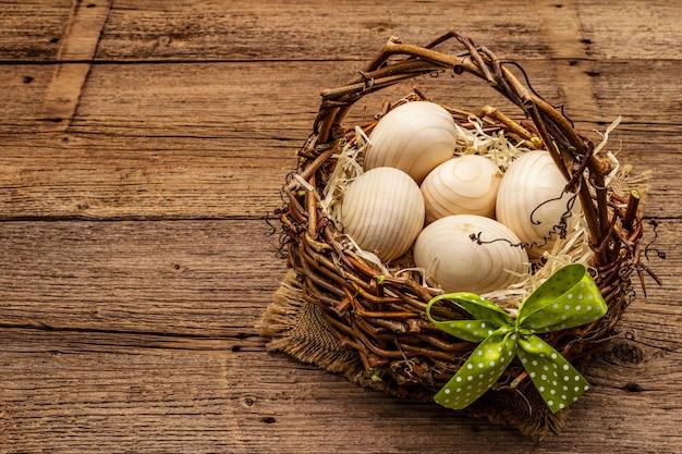 Wielkanocny wiklinowy kosz. zero odpadów, koncepcja diy. drewniane jajka, wióry, satynowa kokardka. stare deski w tle