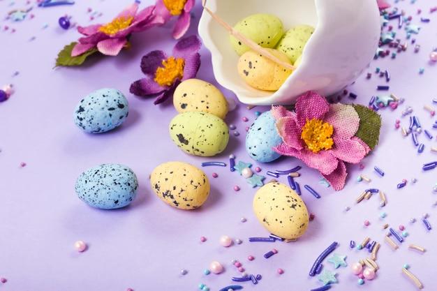 Wielkanocny wystrój w pastelowych kolorach. pisanki, słodycze, słodycze, kwiaty i skorupki.