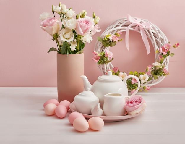 Wielkanocny zestaw herbaty i kolorowe jajka na świątecznym stole.