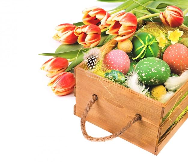 Wielkanocy pudełko z pomarańczowymi tulipanami i wielkanocnymi jajkami na bielu