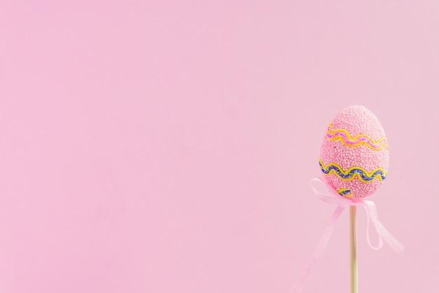Wielkanocy różowy dekorujący jajko na drewnianym kiju na różowym tle. minimalna koncepcja wielkanocy. szczęśliwa kartka wielkanocna