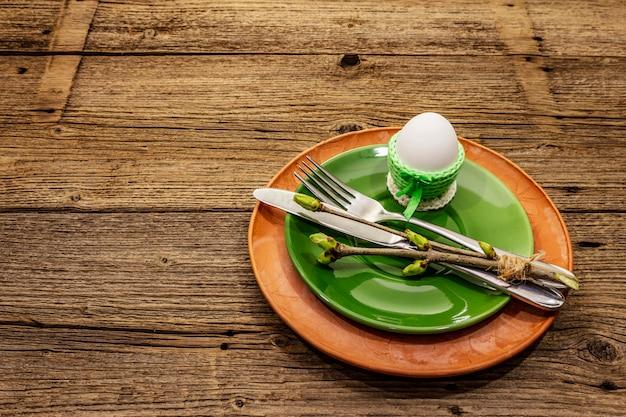 Wielkanocy stołowy położenie na antykwarskim drewnianym tle. szablon karty wakacje wiosna. sztućce, serwetka na szydełku, jajko, gałązki bzu