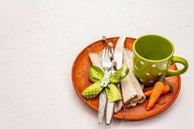 Wielkanocy stołowy położenie na textured białym kitu tle. szablon karty wakacje wiosna. sztućce, kubek, vintage serwetka, jajko, marchewka, królik