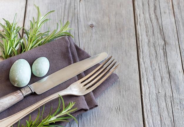 Wielkanocy stołowy położenie z jajkami i rozmarynami na szarym drewnianym stołu zakończeniu up z kopii przestrzenią