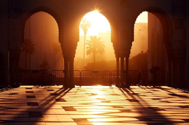 Wielki meczet hassana 2 o zachodzie słońca w casablance, maroko. piękne łuki arabskiego meczetu w zachodzie słońca, promienie słoneczne
