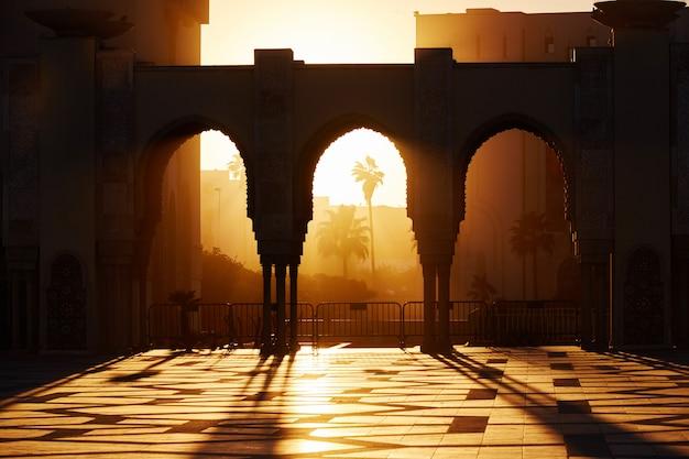 Wielki meczet hassana 2 o zachodzie słońca w casablance, maroko. piękne łuki meczetu arabskiego