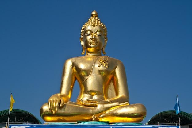 Wielki posąg buddy pod błękitnym niebem.