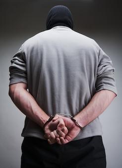 Wielki przestępca zakuty w kajdanki. terrorysta w kominiarce