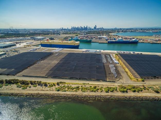 Wielki przewoźnik samochodowy i inne statki przemysłowe zadokowany w port melbourne z panoramą cbd na horyzoncie. melbourne, victoria, australia.
