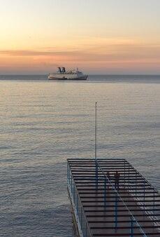 Wielki statek wypływa do morza o świcie różowozłote niebo ludzie na molo ciągną się po horyzont