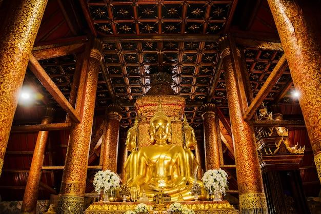Wielki złoty posąg buddy pośrodku sali świątynnej